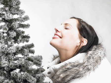 wintery: Woman next to a fir-tree, smiling LANG_EVOIMAGES