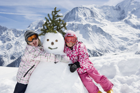 shared sharing: Two girls with a snowman