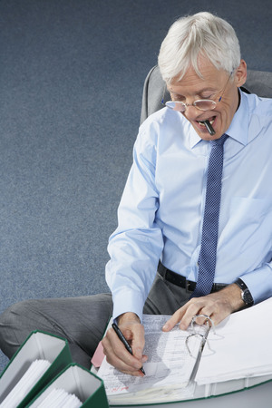 toils: Mature businessman writing