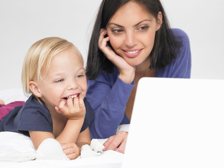 comically: Daughter and mother looking at a laptop