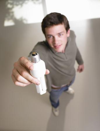 environmentalism: Man fixing a light bulb LANG_EVOIMAGES