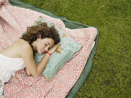 Woman sleeping on blanket outside LANG_EVOIMAGES