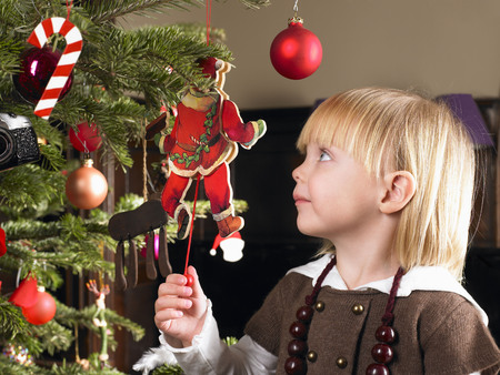 captivation: Girl playing with christmas decoration LANG_EVOIMAGES