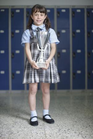 School girl holding trophy LANG_EVOIMAGES