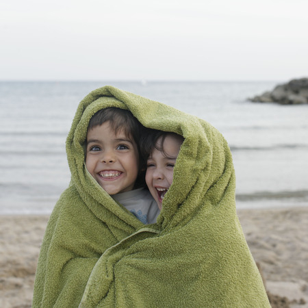 gals: Two young children in towel on beach