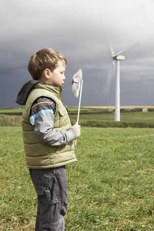 Boy blowing windmill on a wind farm