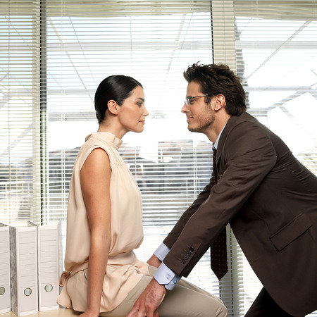 flirtation: Couple facing each other in office LANG_EVOIMAGES