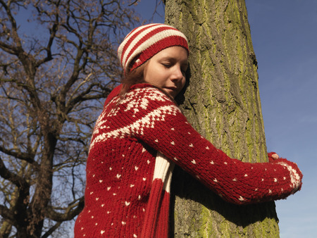 gals: Woman hugging tree, eyes closed LANG_EVOIMAGES
