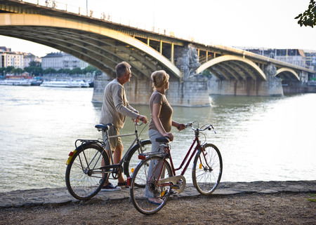 ceasing: Couple by river with bikes