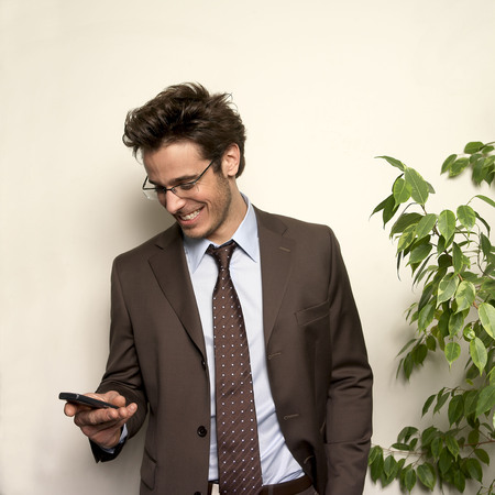 joining forces: Man holding phone in office, smiling
