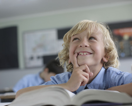 information age: School boy thinking in class