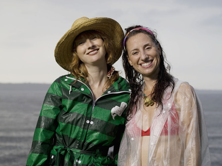 drizzling rain: Two women looking into camera smiling