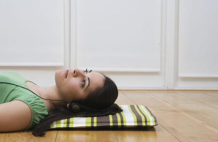 somber: Woman lying on floor listening to music