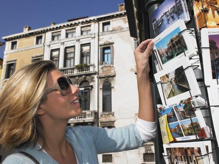 selections: Woman choosing a postcard, smiling