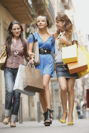 Young women walking with shopping bags LANG_EVOIMAGES