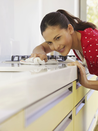 worktops: Young woman cleaning kitchen surface