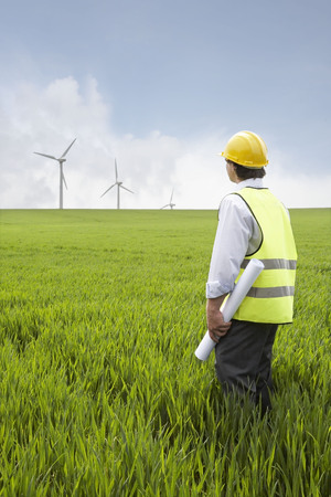accountable: Man holding plans on a wind farm