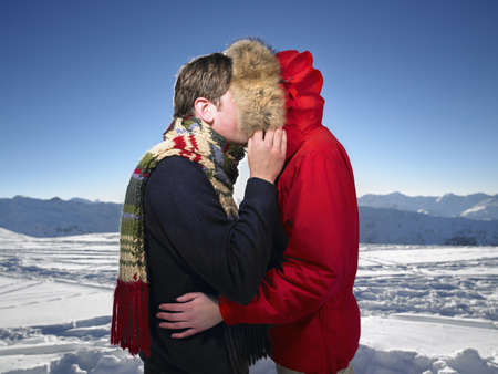 bashfulness: Man kissing woman on mountain top