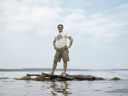 remoteness: Man standing on rocks in water LANG_EVOIMAGES