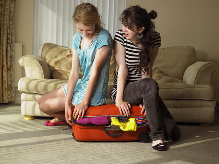 Two females trying to close suitcase