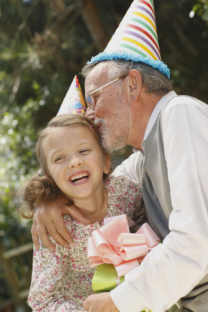 Grandfather kissing grandchild at party