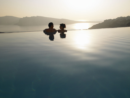 gals: Couple in swimming pool, sunset LANG_EVOIMAGES