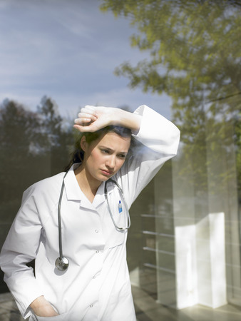 Young female doctor by the window LANG_EVOIMAGES