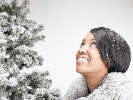 gals: woman next to a fir-tree, smiling