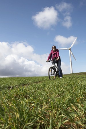Woman riding a bike on a wind farm LANG_EVOIMAGES