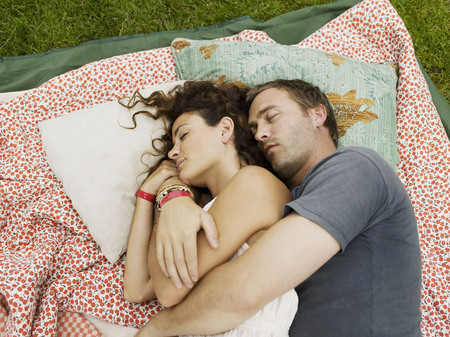 Man and woman sleeping on blanket