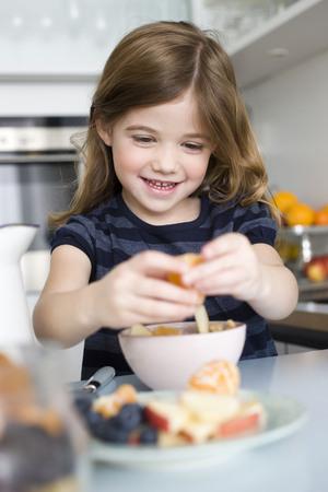 Girls putting fruit into her yogurt