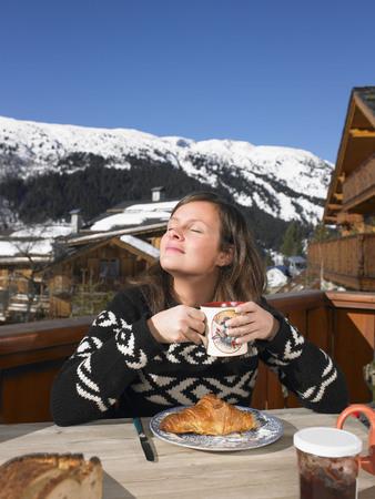 adventuresome: Young woman having breakfast on terrace