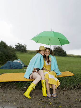 shared sharing: Two women sitting under umbrella