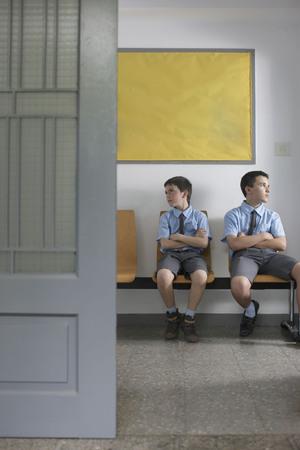 School boys sitting outside office