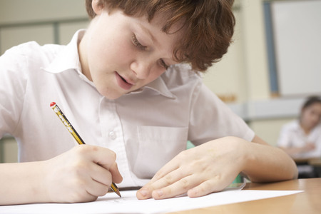 Boy writing in classroom LANG_EVOIMAGES