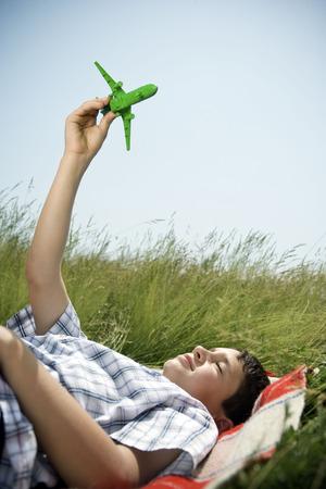 accountable: Boy lying down playing with plane