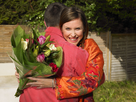 gals: Woman with flowers hugging man LANG_EVOIMAGES