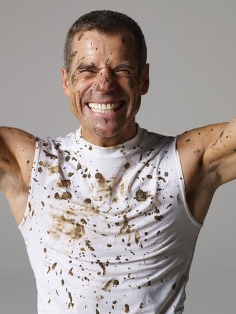 warming up: Joyous mud covered man
