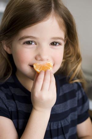 jesting: Girl holding tangerine