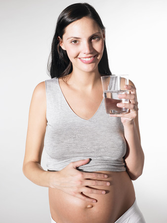 rejuvenated: Pregnant woman with a glass of water
