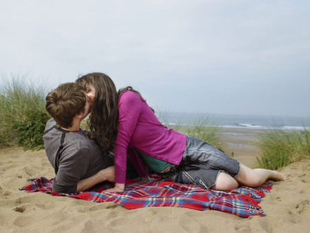gals: Couple kissing on blanket on sand dune