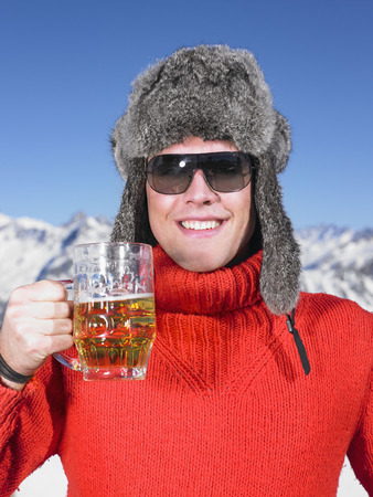 Young man having drink at mountains LANG_EVOIMAGES