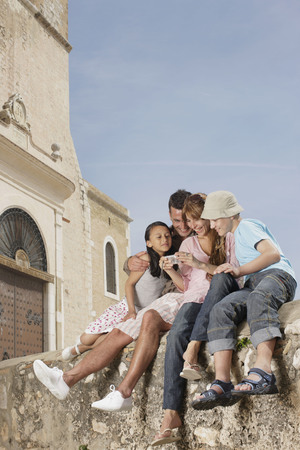 sightseers: Family sitting on wall sharing photos