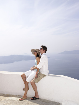 honeymooner: Couple leaning on a low wall, sea view