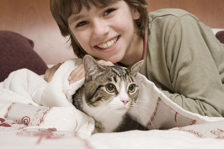 enclose: Young boy with pet cat