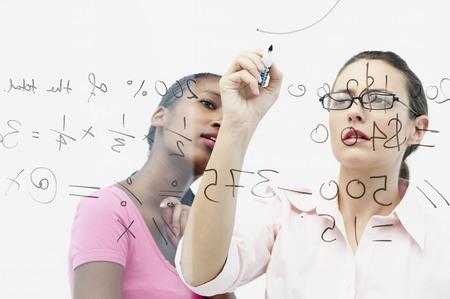 formulae: Two women write on glass panel
