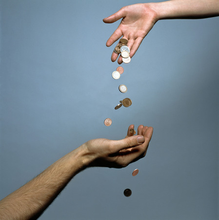 Hands dropping coins