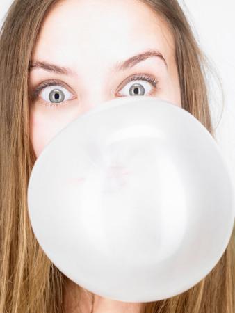 Woman blowing up a bubble gum LANG_EVOIMAGES