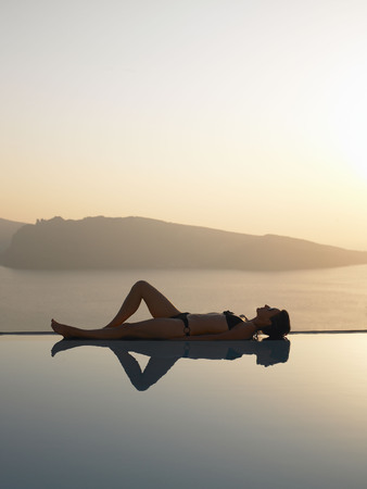 Woman laying on the edge of a pool LANG_EVOIMAGES