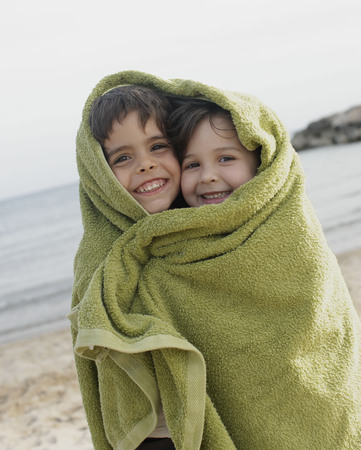 sightseers: Two young children in towel on beach